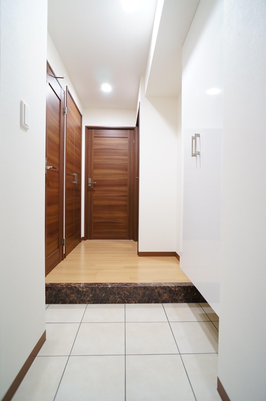 白基調と木目ドアの広々とした玄関